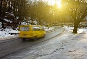 stock photo of slippery-roads  - Yellow van driving on wet slippery road from melted snow - JPG