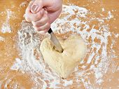 Hand With Knife Struck Heart Of Dough