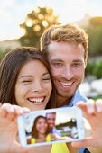 Couple in love taking selfie photo with smartphone. Romantic mixed race couple taking selfies pictures with smart phone camera having fun together outdoors in park. Asian girl, Caucasian guy.