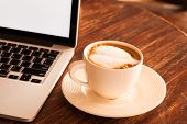 image of latte  - Hot latte coffee cup in a white cup on a table laptob in coffee shop - JPG