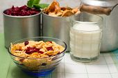 image of milk glass  - Horizontal photo of cornflakes with dried cranberries in glass blue bowl placed on green cloth - JPG