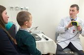 picture of infirmary  - boy sits in mothers lap at medical check in front of a doctor with autorefractometry - JPG