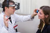 picture of infirmary  - ophthalmologist examines the eyes of a woman through a magnifying glass - JPG