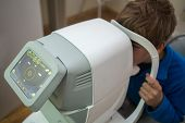 stock photo of infirmary  - boy tests his eyes at Auto - JPG