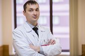 picture of infirmary  - male physician closeup portrait with arms across - JPG