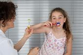 stock photo of ten years old  - Smiling young girl of ten years old brushing teeth - JPG