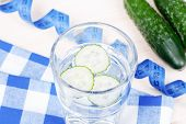 pic of cucumbers  - Glass of water with slices of fresh cucumber on checkered napkin beside centimeter and two cucumbers top view - JPG