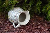 pic of jug  - The antique jug with a pattern of flowers lies on brown chipped wood under a fir - JPG