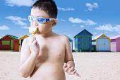 picture of naked children  - Closeup of naked child wearing swimming glasses on the beach while enjoying a delicious ice cream - JPG