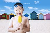 picture of beach hut  - Portrait of naked little boy enjoying a tasty ice cream on the seaside with the background of the beach huts - JPG