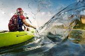 stock photo of paddling  - Young lady paddling hard the kayak with lots of splashes - JPG