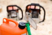 foto of chainsaw  - Close up of orange plastic fuel canister with two chainsaws in background - JPG