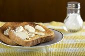 image of salt shaker  - Two slices of white buttered toast on a plate with salt - JPG