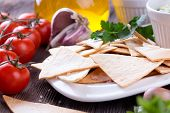 pic of nachos  - Tradition Mexican Tortilla Chips nachos with handmade guacamole sauce on wooden table - JPG