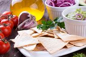 foto of nachos  - Tradition Mexican Tortilla Chips nachos with handmade guacamole sauce on wooden table - JPG