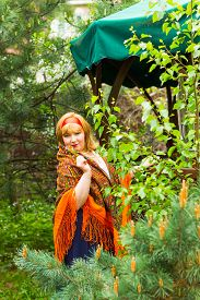 stock photo of cheeky  - Cheeky Russian cheerful young woman in the green of spring foliage with a scarf draped pavlopasadskim oranzhegogo color with forget - JPG