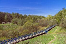 stock photo of ravines  - Pedestrian bridge over the marshy ravine - JPG