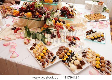 Постер, плакат: Банкетный стол полный сладости фрукты и ягоды, холст на подрамнике