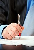 This is businessman with pen signing contract