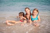 Постер, плакат: Three Happy Children Playing On The Beach