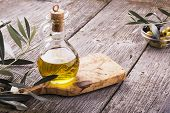 Постер, плакат: Jug with extra virgin olive oil on cutting board surrounded by branches