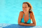 Smiling Girl In Blue Bikini With Brown Curly Hair Stands In Swimming-pool And Looks In Direction