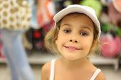 Portrait Of Little Girl Trying White Cap In Store And Smiling, Counter With Commodity