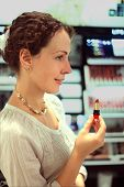 Beautiful Young Woman Chooses Red Lipstick In Store, Holding Lipstick