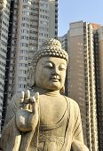 stock photo of budha  - Budha situated between apartment buildings in Beijing China - JPG