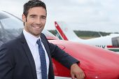 Young businessman standing in front of an airplane