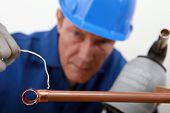 skilled tradesman in blue jumpsuit is soldering a copper pipe