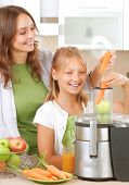 stock photo of juicer  - Happy Family making fresh apple and carrot juice - JPG