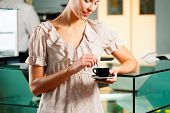 Woman in a coffeeshop or cafe enjoys her cappuccino