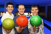 Friends stand alongside and ahead in hands hold balls for bowling