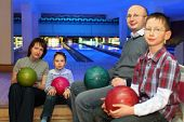 Mother, father and two children, sit in club and hold balls for bowling on knees, focus on  girl and
