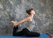 Young Woman Doing Yoga Posture Kapotasana Or Pigeon Pose Variation 1