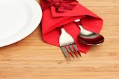 cutlery and napkin on wooden background