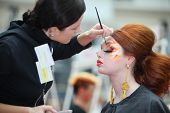 MOSCOW - OCTOBER 2: Visagiste makes original makeup for redheaded model at XVII International Festival