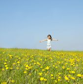 Little girl running on a meadow in a field of flowers, dandelions