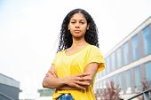 Serious Confident Student Girl Standing For Camera With Folded Arms. Young Latin Woman In Bright Cas poster