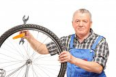 Middle aged man holding wrench and repairing bicycle wheel isolated over white background