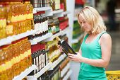 stock photo of department store  - woman choosing bio food olive oil in grocery shopping store - JPG