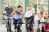 Senior group on spinning bikes in gym holding thumbs up