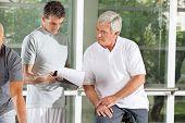 Fitness instructor explaining training plan for senior in gym