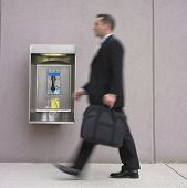 Blurred image of businessman walking by payphone