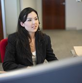 Mulher sentada no escritório usando o fone de ouvido