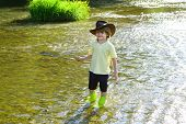 Cute Little Boy Fishing On Pond. Young Man Fly Fishing. Photo Of Little Boy Fishing. Boy In Yellow S poster