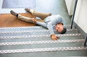 Mature Man Lying On Staircase After Slip And Fall Accident poster