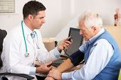 American doctor taking senior man's blood pressure