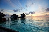 resort maldivian houses on sunrise